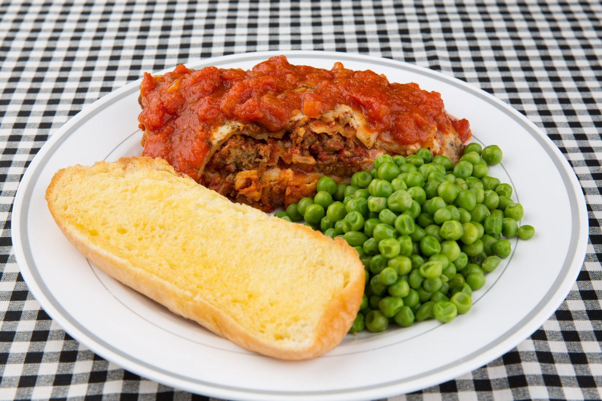 lasagna, green peas, and garlic on white plate and black plaid tablecloth
