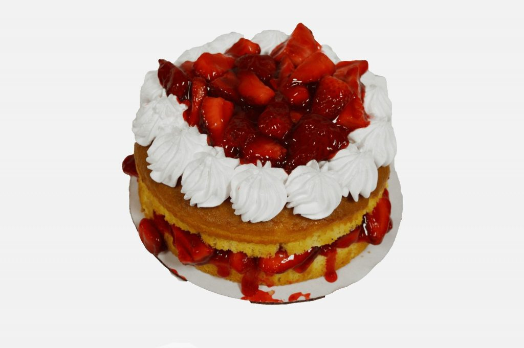 cake topped with strawberry sauce and whipped cream