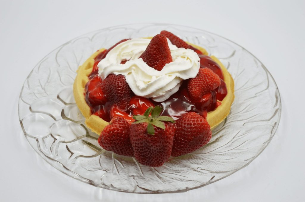 waffle topped with strawberry sauce and whipped cream
