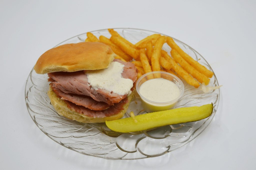 ham sandwich with french fries and a pickle spear