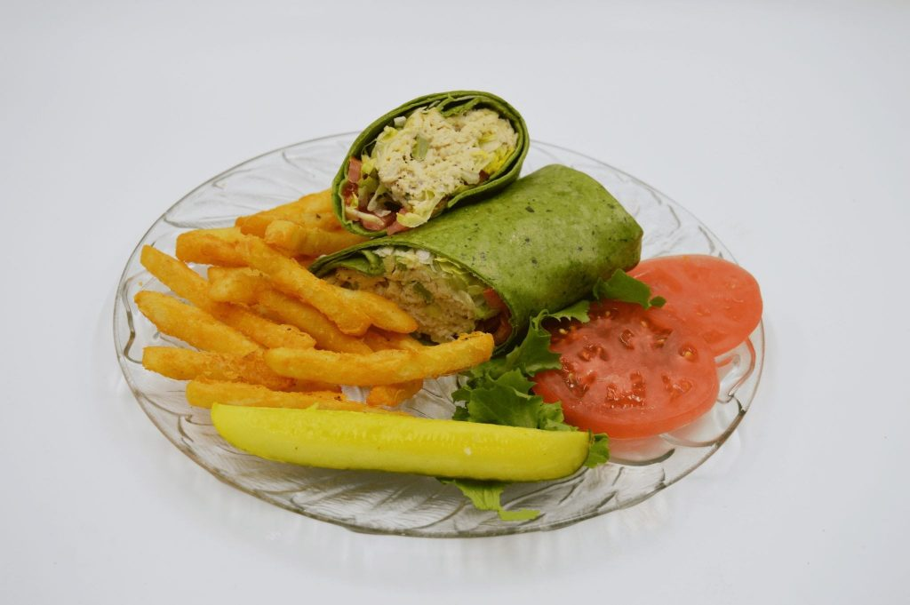 spinach wrap with french fries and pickle spear
